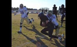 Jaran Richman #15 tackles the ball carrier near the Hornet sideline in front of Telly Harper #88.