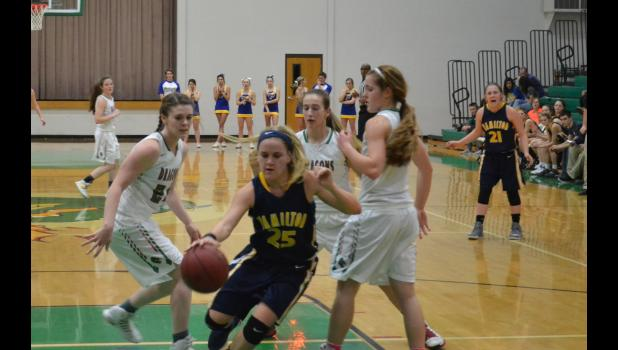 Mckauley Prothero #25 dribbles away from 3 Dragon defenders.