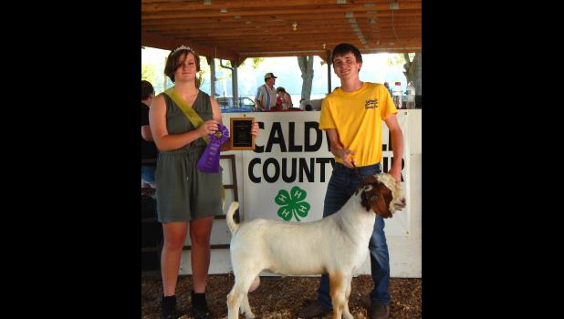 Carter Williams is presented a championship ribbon by Queen Madison Rechtermann for his Grand Champion buck at the CC Fair.